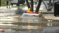 Fire Fighters Drive The Fire Truck Through A Huge Flood