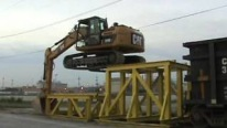 Skilled Cat Operator is Climbing on to a Rail Car Like a Boss
