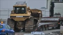 Caterpillar Bulldozer Slides Down Off A Truck