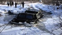 Insane Russian Guy Drives His ATV Through a Frozen River and Breaks the Ice